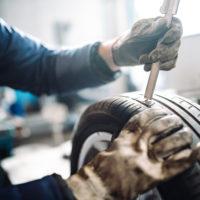Tire mechanic taking a precise measurement